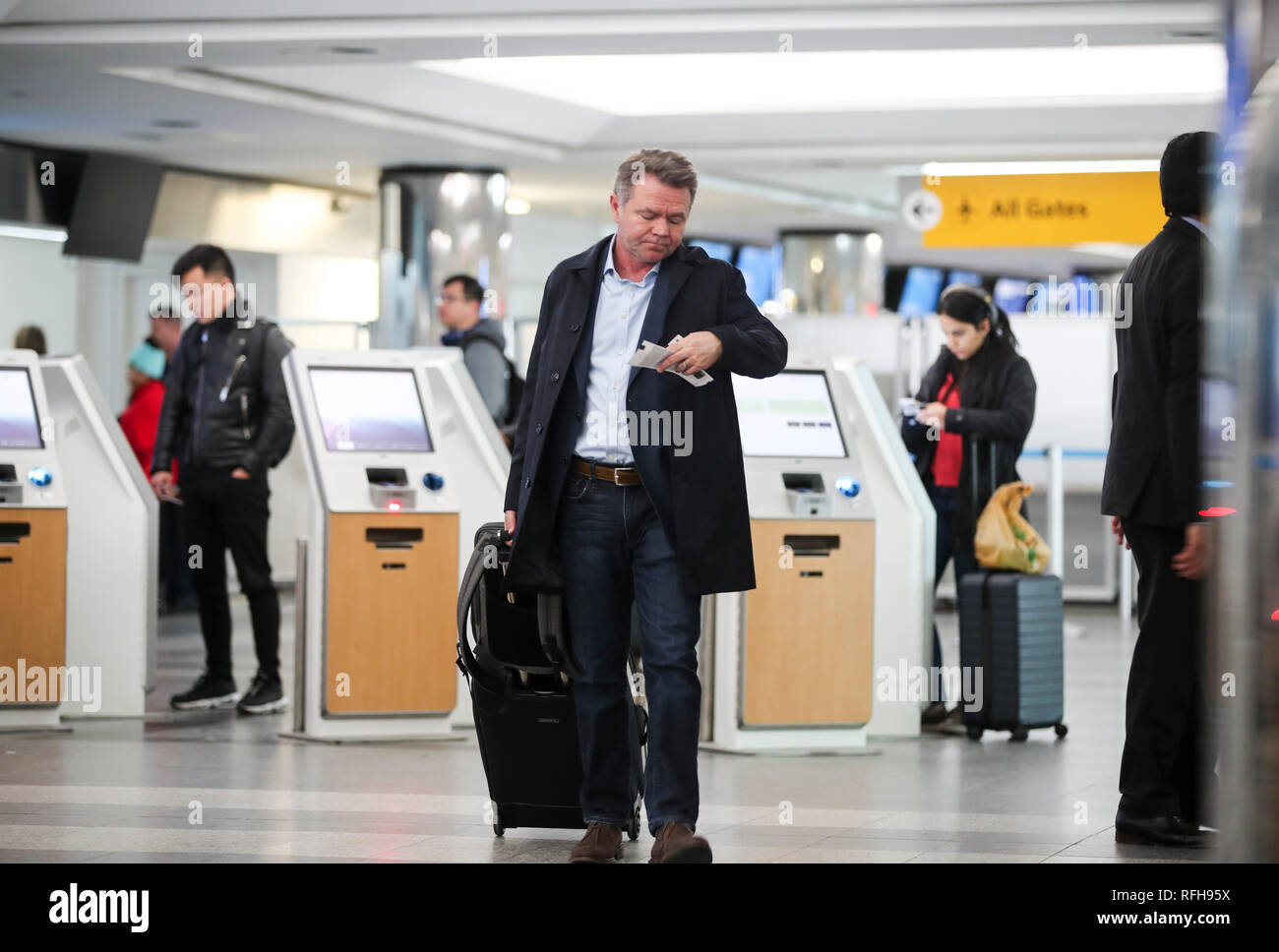 New York, USA. 25th Jan, 2019. A passenger checks his airline ticket at the LaGuardia Airport in New York, the United States, on Jan. 25, 2019. The U.S. Federal Aviation Administration on Friday halted flights bound for New York City's LaGuardia Airport, due to staff shortage caused by the historic government shutdown. Credit: Wang Ying/Xinhua/Alamy Live News - Stock Image