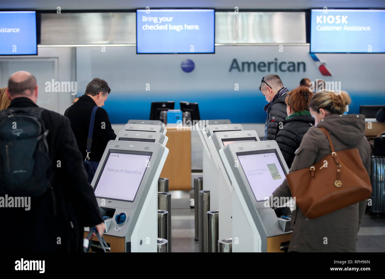 New York, USA. 25th Jan, 2019. Passengers use self-service kiosks to check in at the LaGuardia Airport in New York, the United States, on Jan. 25, 2019. The U.S. Federal Aviation Administration on Friday halted flights bound for New York City's LaGuardia Airport, due to staff shortage caused by the historic government shutdown. Credit: Wang Ying/Xinhua/Alamy Live News - Stock Image