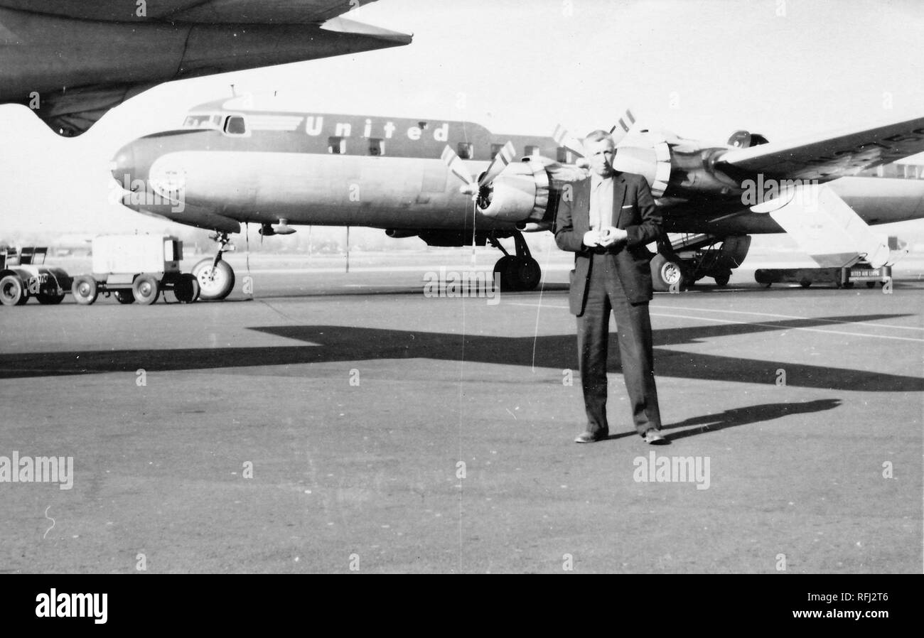 Black and white photograph of a light-haired, middle-aged man, wearing a dark suit, seen in full-length view, posing in the middle of an airport runway or tarmac, with a luggage trolley and a large passenger airplane with the logo 'United' visible in the background, photographed during a hunting and fishing trip located in Alaska, 1955. () - Stock Image