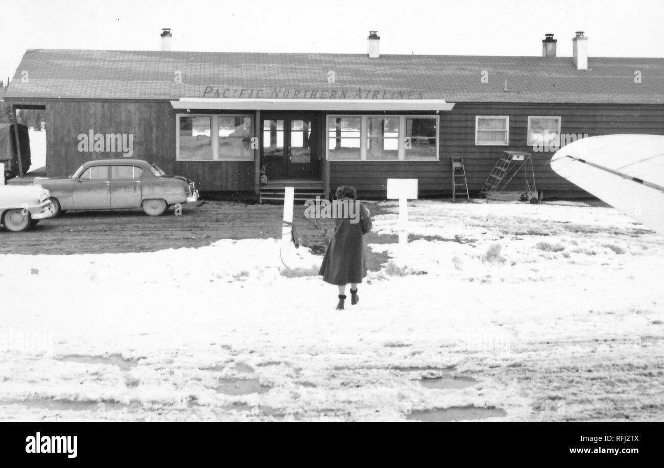 Black and white photograph of a woman, shot from behind, in full-length view, wearing a long, dark coat and fur-trimmed boots, walking across snow-covered ground toward the open door of a wooden, single-story airport terminal marked 'Pacific Northern Airlines, ' with the wing of an airplane visible in the right foreground, photographed during a hunting and fishing trip located in Alaska, 1955. () - Stock Image