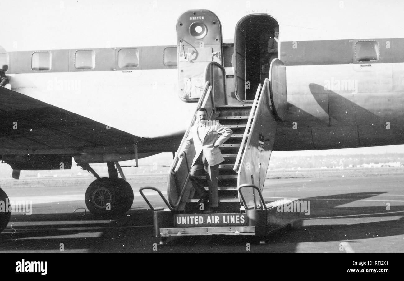Black and white photograph of a dark-haired, middle-aged man, seen in full-length view, wearing a suit, standing in contrapposto pose with one hand on his waist, on the lowest step of a flight of airplane stairs or gangplank, with a member of the cabin crew partially visible in the open airplane door in the background, and the logo 'United Air Lines' visible on the lowest riser beneath the man's feet, photographed during a hunting and fishing trip located in Alaska, 1955. () - Stock Image