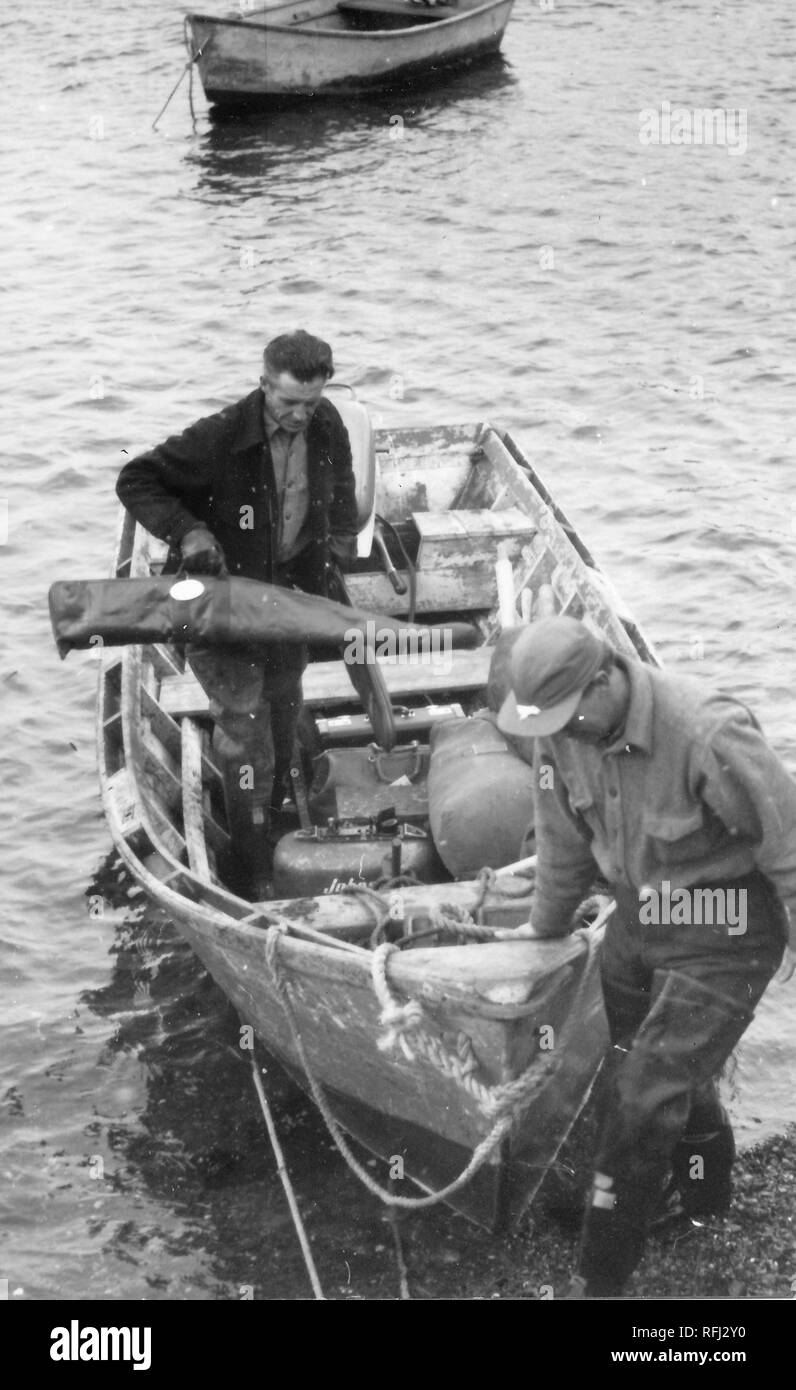 Black and white photograph of two middle-aged men, one man in the foreground looking downward as he steadies the bow of a dinghy that is pulled to the shoreline, a second, dark-haired man, carrying a rifle bag, navigates the hull in order to reach the bow, with water and an anchored dinghy visible in the background, photographed during a hunting and fishing trip located in Alaska, 1955. () - Stock Image