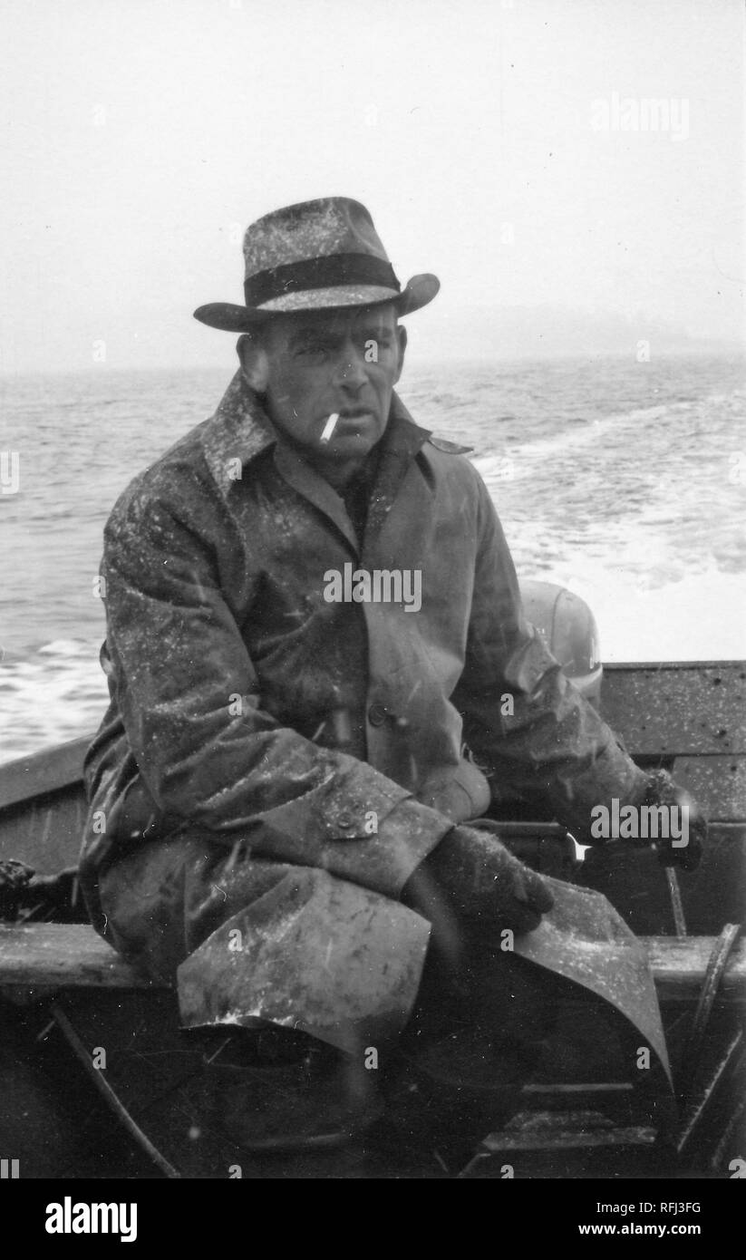 Black and white photograph of a middle-aged man, with a cigarette between his lips, wearing a snow-dusted coat, gloves, and hat, sitting in the stern of an open dinghy, steering the tiller of an outboard motor with one hand, with a light wake and a shadowy outline of land visible in the background, photographed during a hunting and fishing trip located in Alaska, 1955. () - Stock Image
