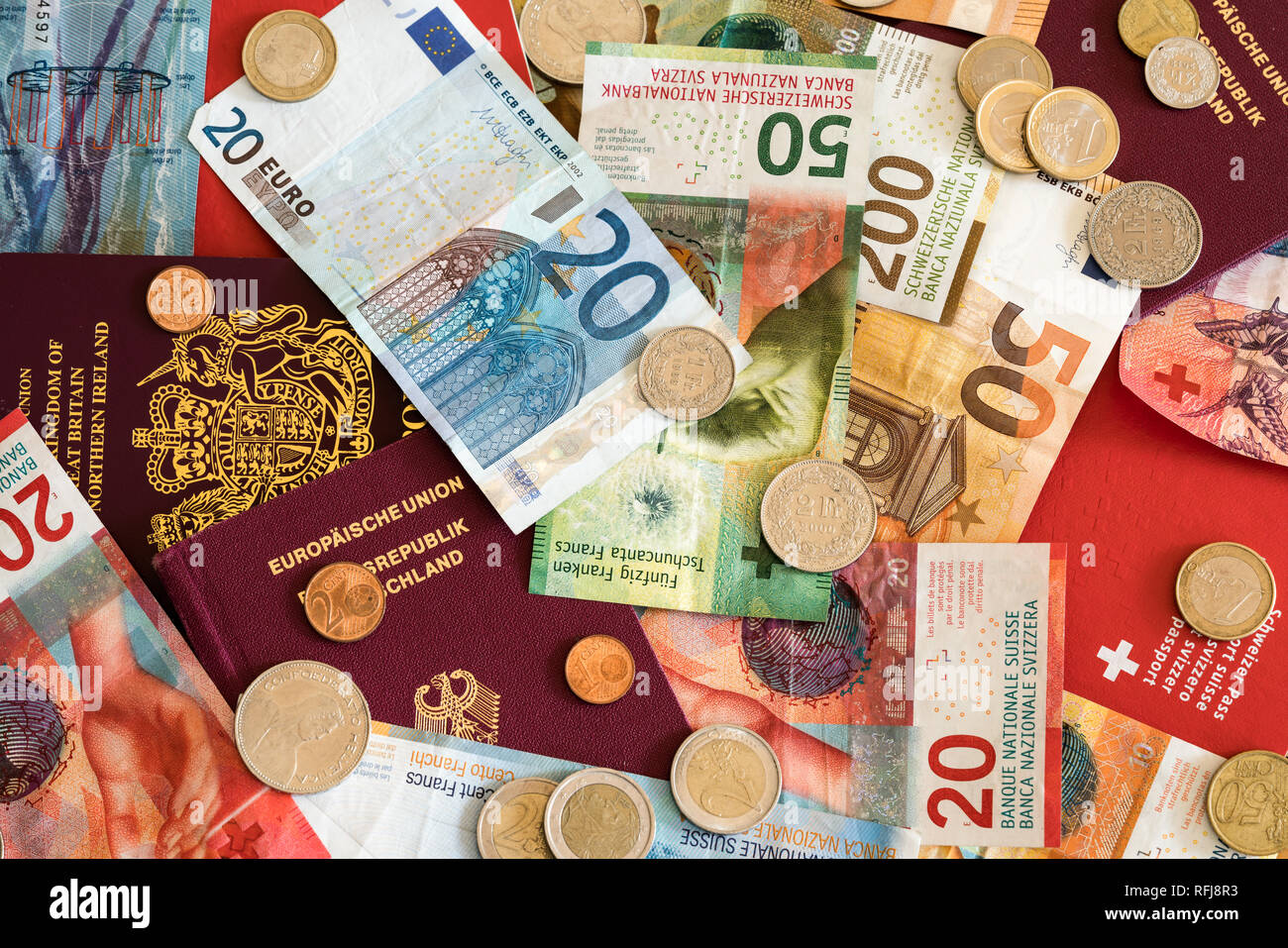 European passports and Swiss franc and Euro coins and bills mixed close up background - Stock Image
