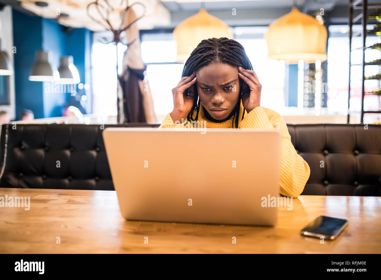 Young african woman with laptop suffering of headache while sitting in cafe Stock Photo