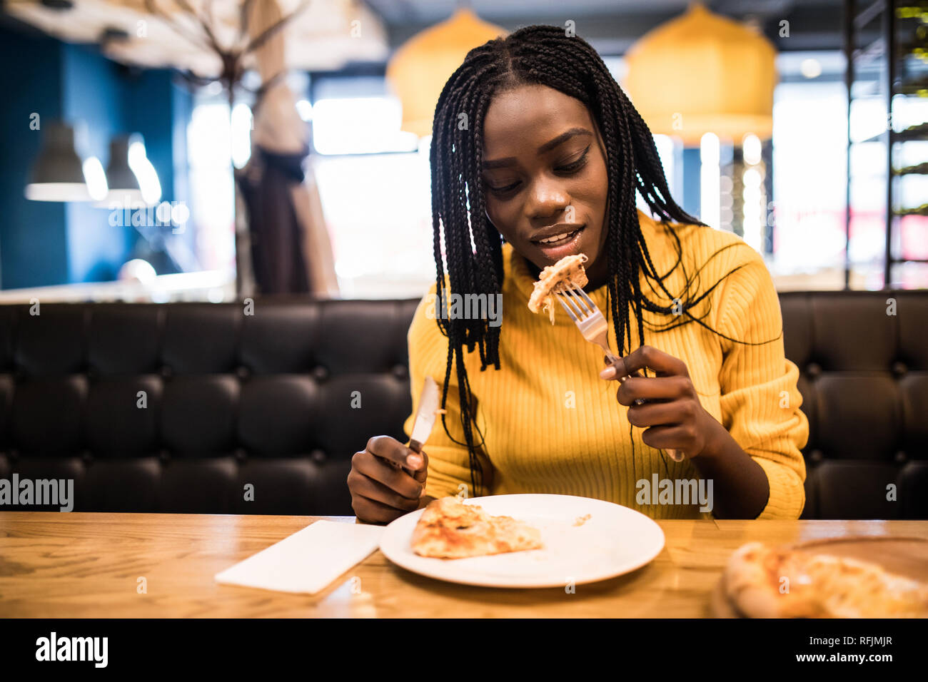 Young afro american woman wearing in yellow sweater eating pizza in cafe Stock Photo