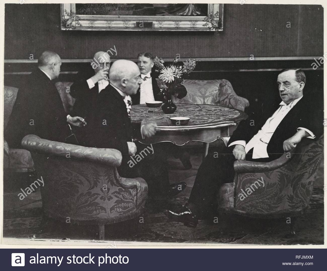 [Five Gentlemen Conversing around Table]. Artist: Erich Salomon (German, Berlin 1886-1944 Auschwitz, Poland). Dimensions: 17.4 x 23.2 cm. (6  7/8  x 9  1/8  in.). Date: 1920s-30s.  The phrase 'candid camera' was first coined in 1929 to describe Salomon's idiosyncratic technique of capturing the world's most powerful political and industrial leaders revealing themselves as ordinary human beings: talking, yawning, and joking. With his 35mm Ermanox camera concealed (sometimes in a hat or suitcase) and his unobtrusive appearance, Salomon was able to cut through the slick facade conveyed by officia - Stock Image