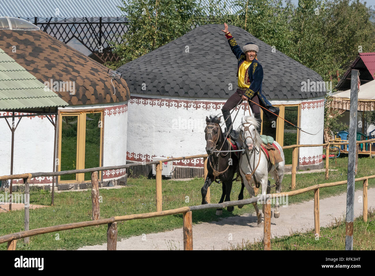 Kazakh trick rider on two horses, riding by yurts, Alamty, Kazakhstan Stock Photo
