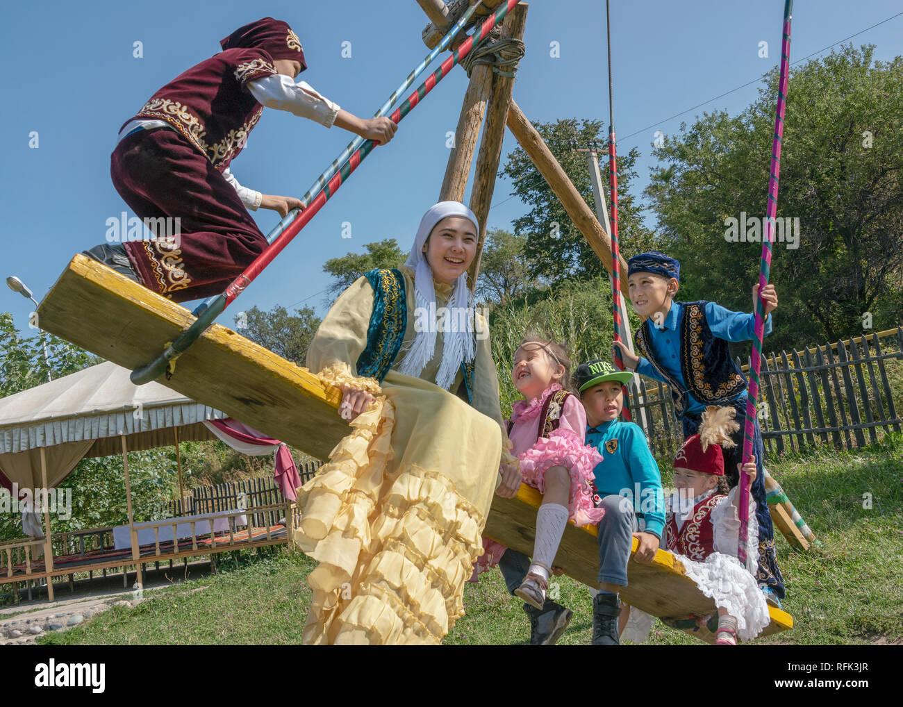 Fun on a swing, young Kazakhs in festive attire, Almaty, Kazakhstan - Stock Image