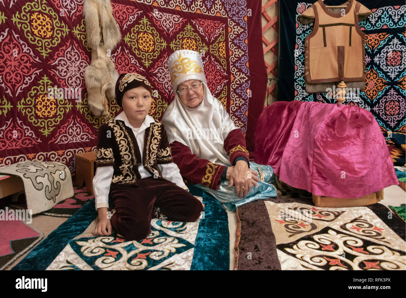 Grandmother and grandson in traditional attire inside a yurt, Almaty, Kazakhstan - Stock Image