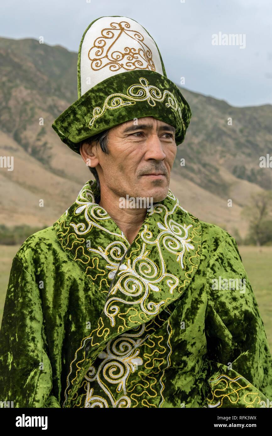 Kazakh man in green, near Kolsay Lake, Kazakhstan - Stock Image