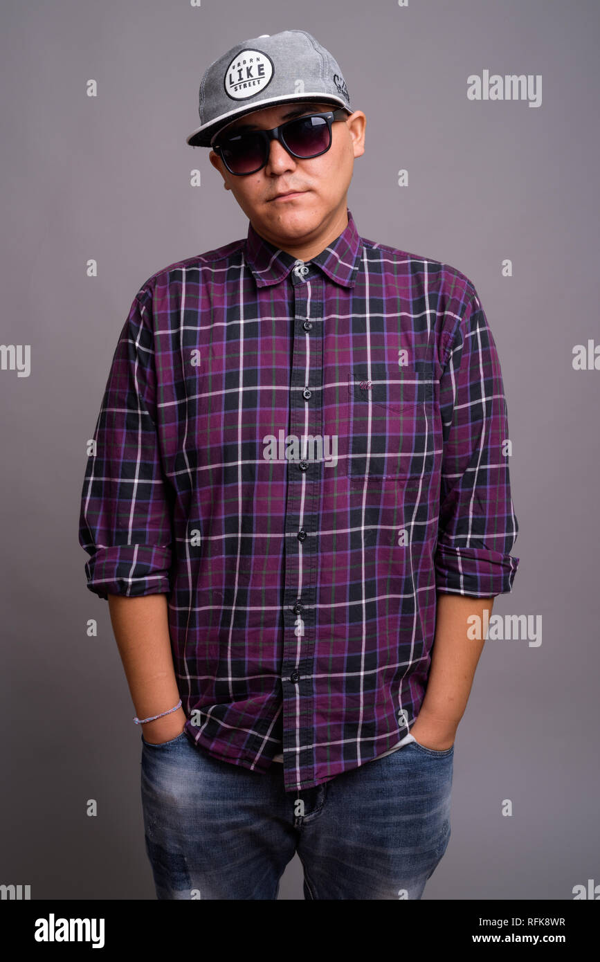 Young Asian gangster man against gray background - Stock Image