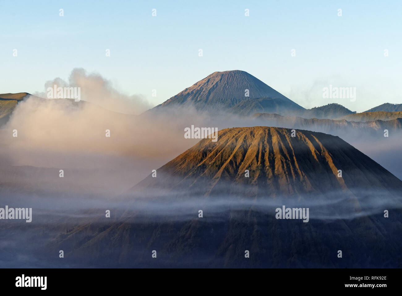 View in the morning light on a volcanic mountain surrounded by clouds and fog with strongly structured flanks - Location: Indonesia, Java, Mt. Bromo - Stock Image