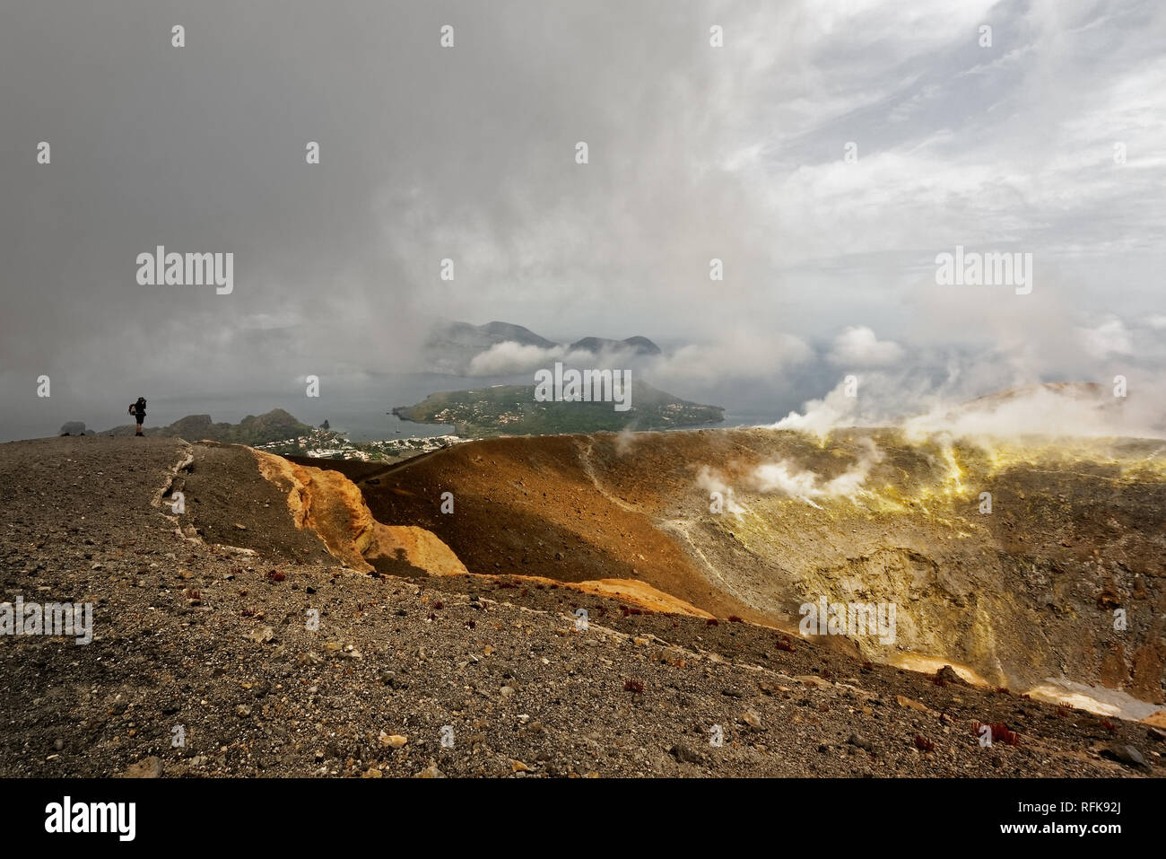 Wide view of the crater rim over the Aeolian Islands in the Mediterranean, dramatic clouds and sulfur fumes, person as a scale - Location: Italy, Aeol - Stock Image