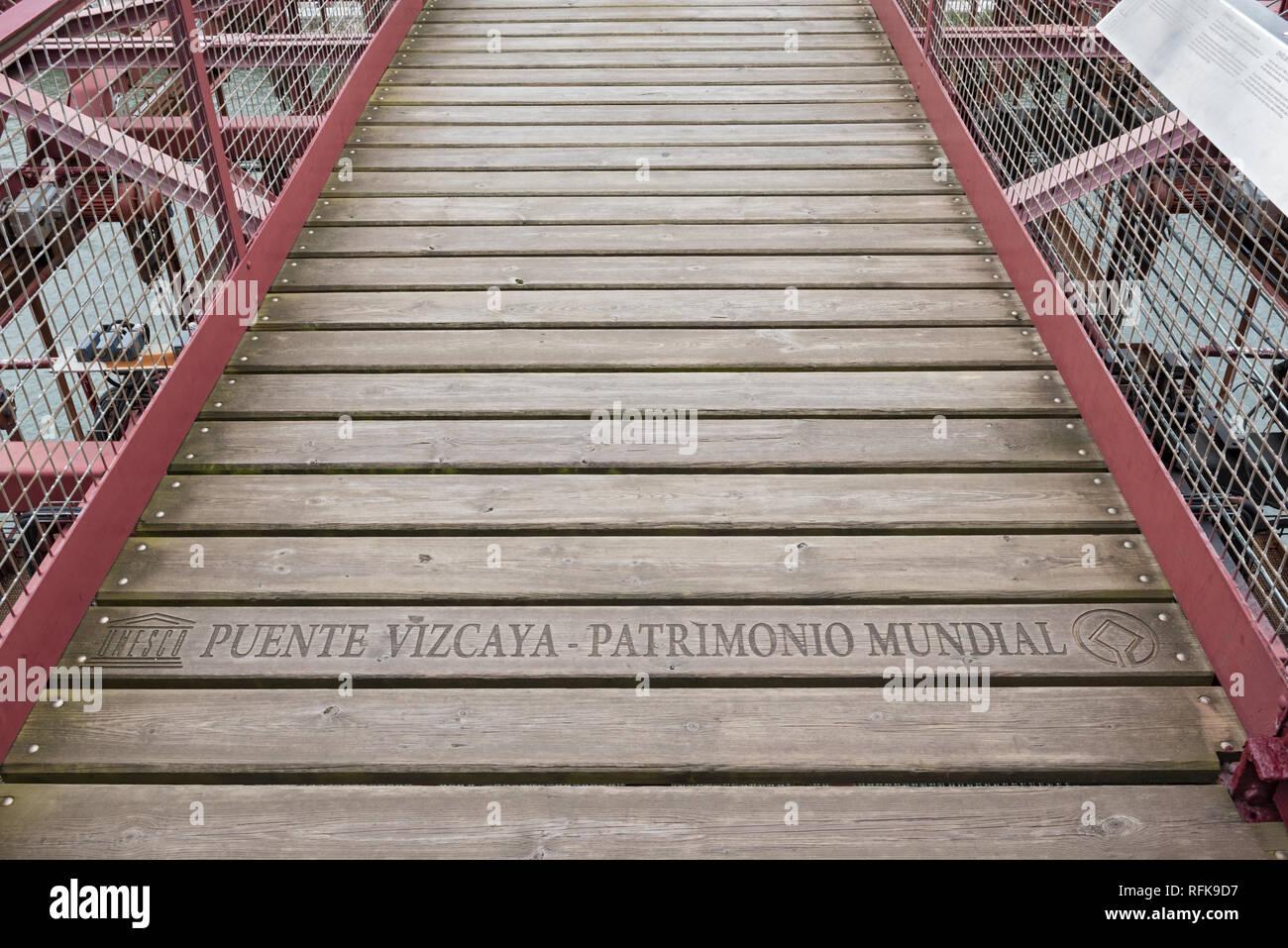 lettering (unesco puente vizcaya-patrimonio mundial) on the suspension bridge of bizkaia (puente de vizcaya) between getxo and portugalete above the r - Stock Image