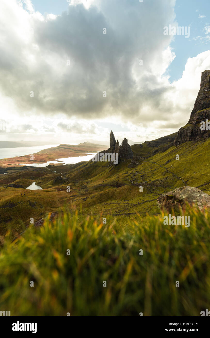 Old Man of Storr with grass foreground and the sun bursting through dramatic clouds during autumn (Isle of Skye, Scotland, United Kingdom) - Stock Image