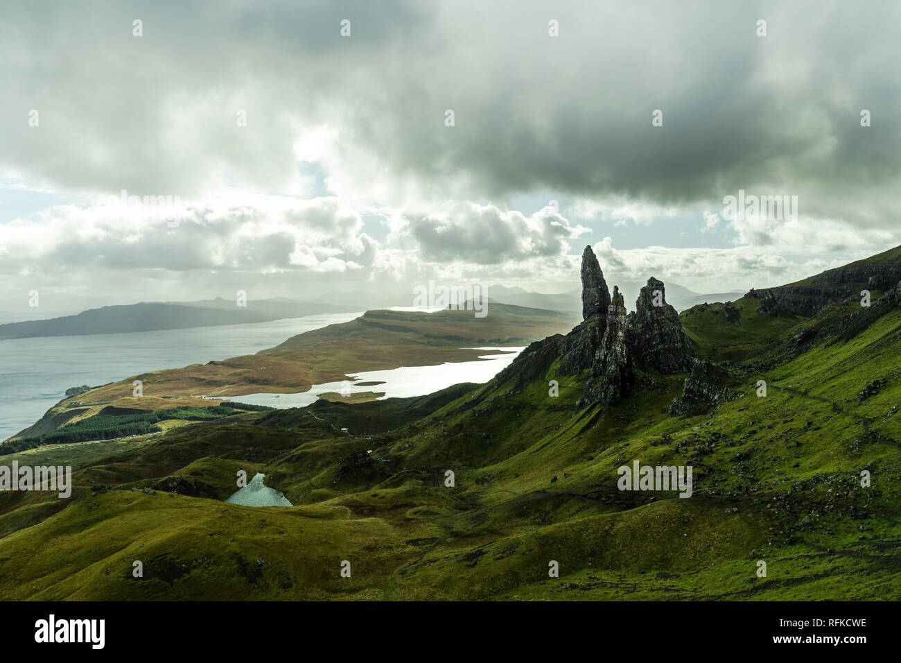 Panorama view of Old Man of Storr as seen from a higher viewpoint with dramatic clouds during autumn (Isle of Skye, Scotland, United Kingdom) - Stock Image