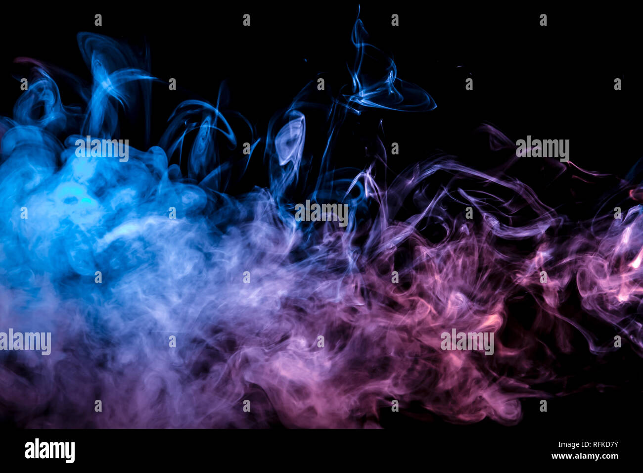 Thin smoothly curling streams of colored smoke evaporate against a black background illuminated with blue and pink light like tongues of fire. - Stock Image