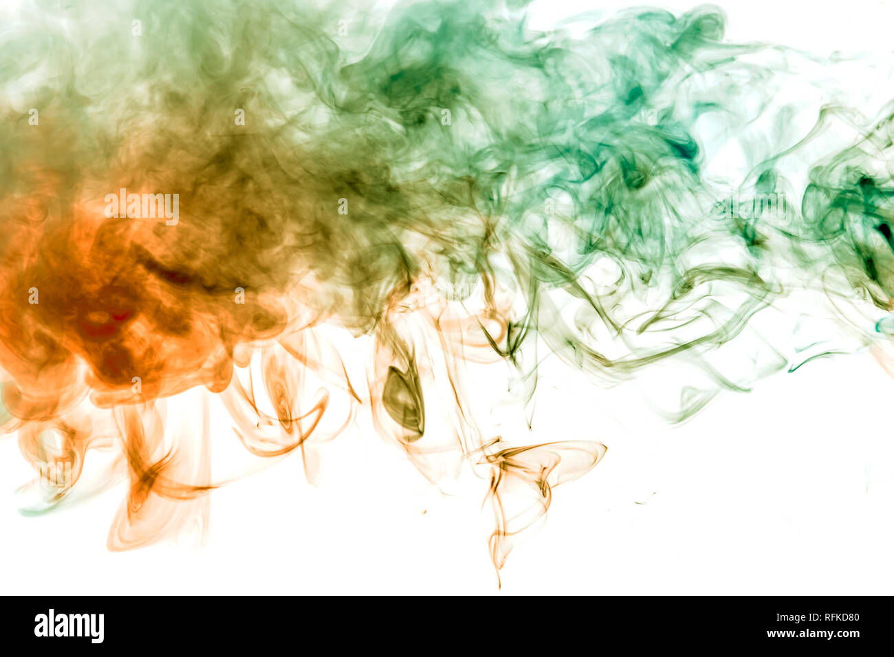 Thin smoothly curling streams of colored smoke dissolve on a white background like watercolor backlit with orange and green light. - Stock Image