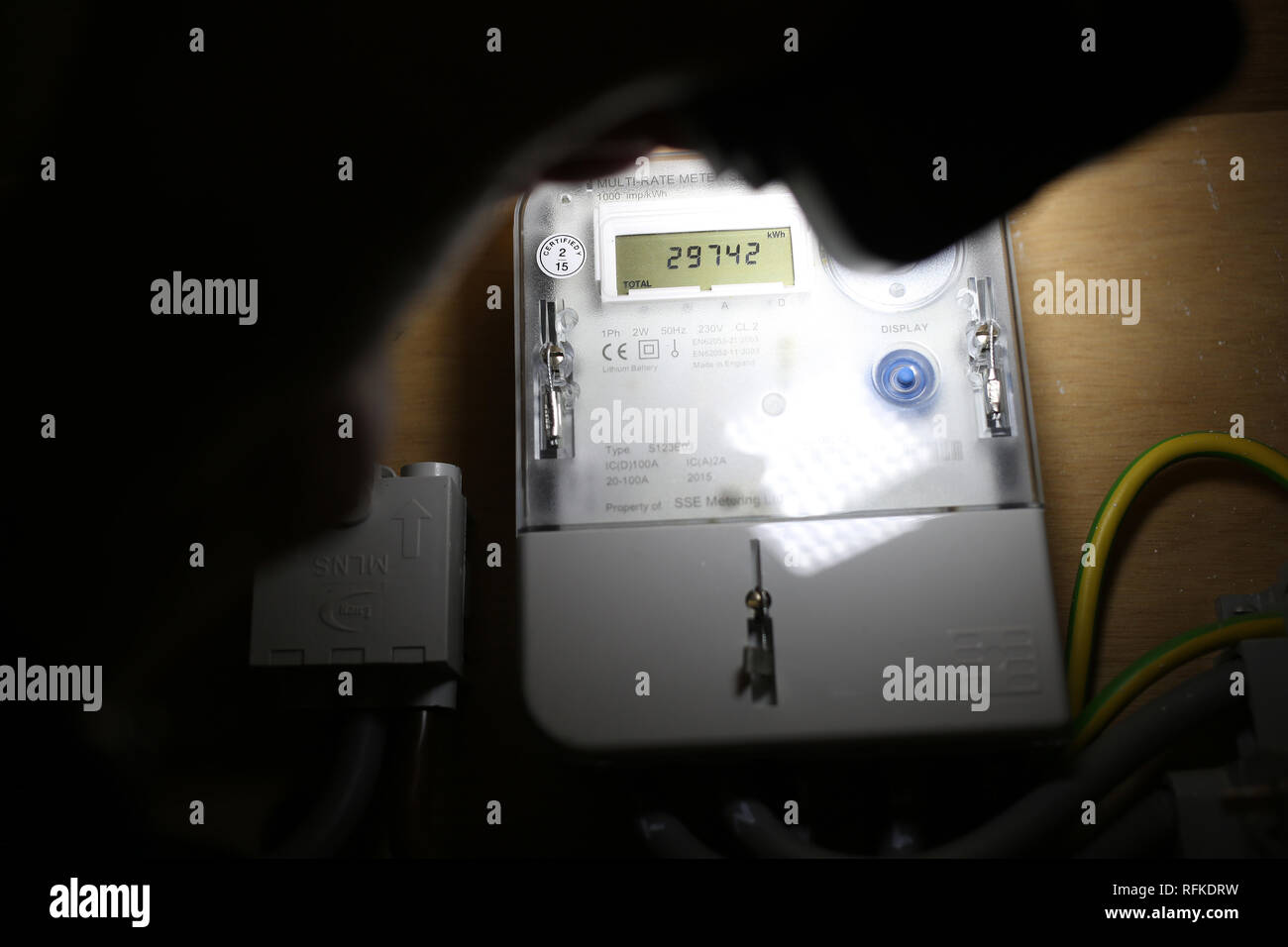 Non Smart Electricity meter reading  by torchlight - Stock Image