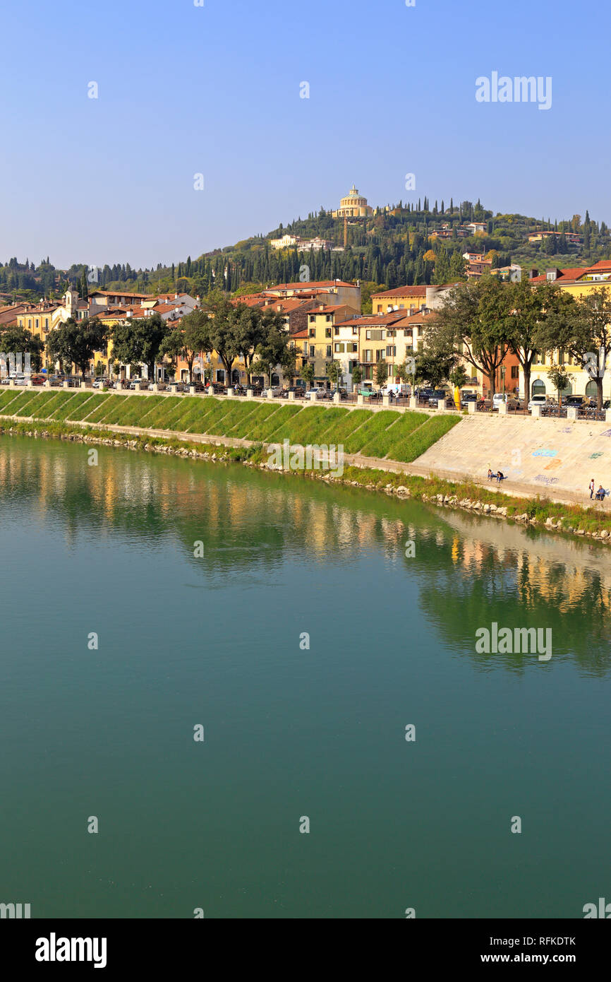 Adige River and distant hilltop Sanctuary our Lady of Lourdes from the Ponte Pietra, Verona, Veneto, Italy. Stock Photo