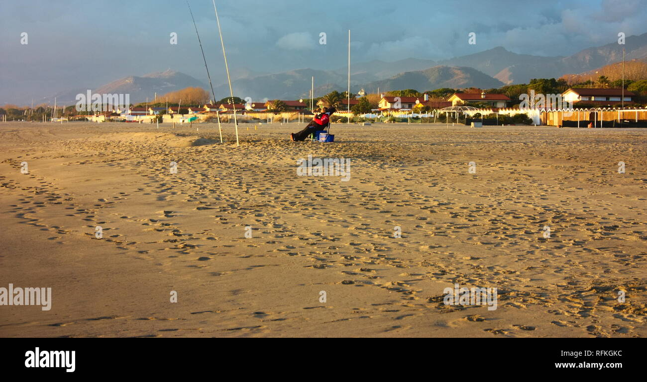 at dusk or sunset an experienced fisherman enjoys a well-deserved break on the sandy beach of the sea. he threw the hook and waits for the fish to cat - Stock Image