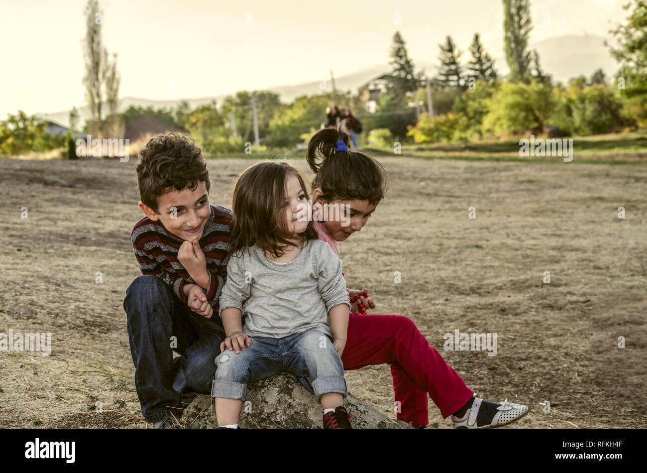 Ashtarak,Armenia,10 September,2018:Two little girls and little boy met and became friends in the courtyard of Saghmosavank Church in the autumn evenin Stock Photo