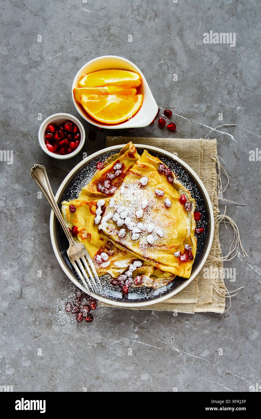 Flat lay of crepes in plate topped with pomegranate and sugar. Homemade thin pancakes and fruits - Stock Image
