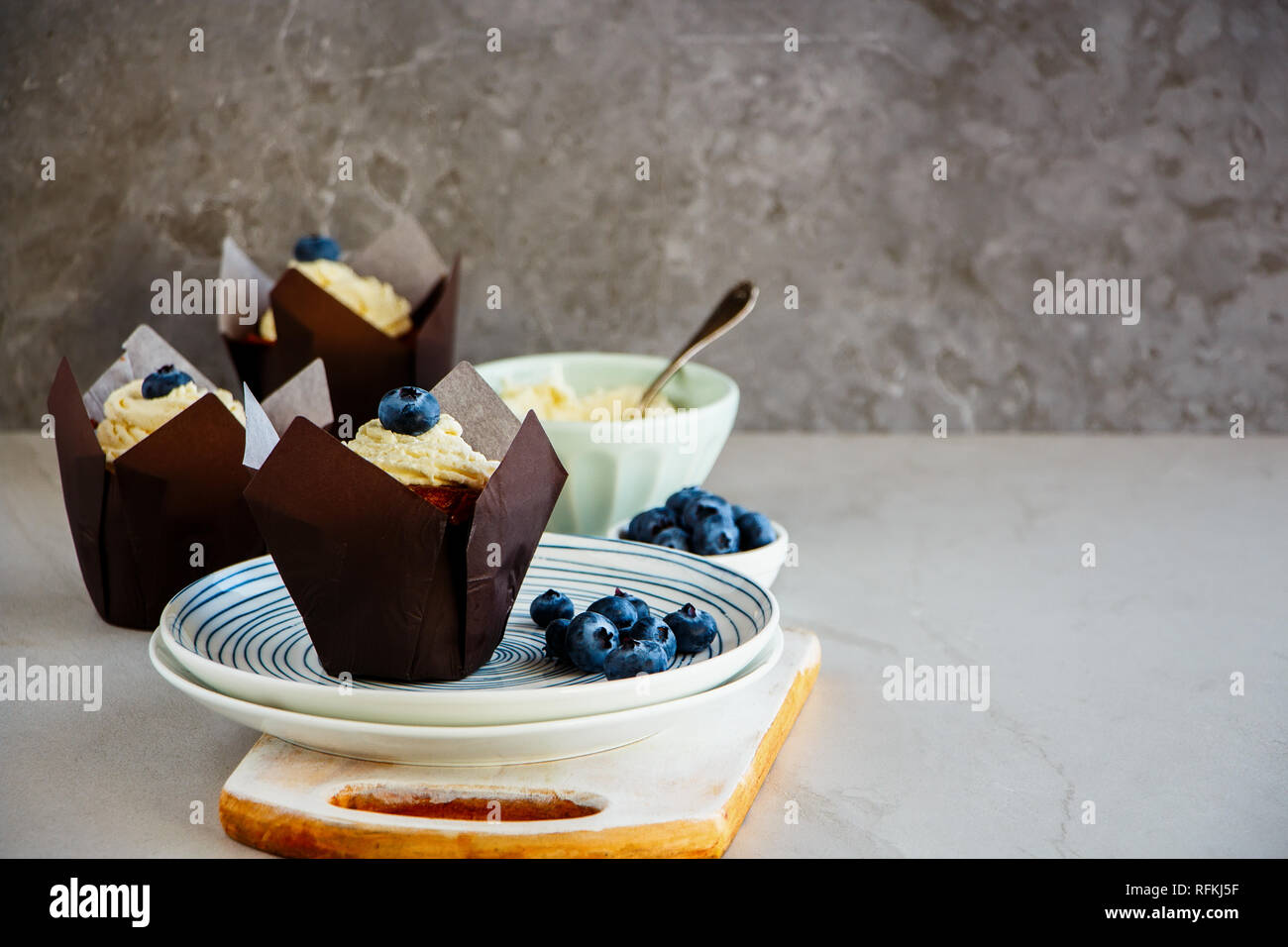 Three frosting cupcakes decorated with cream cheese and fresh blueberry Stock Photo