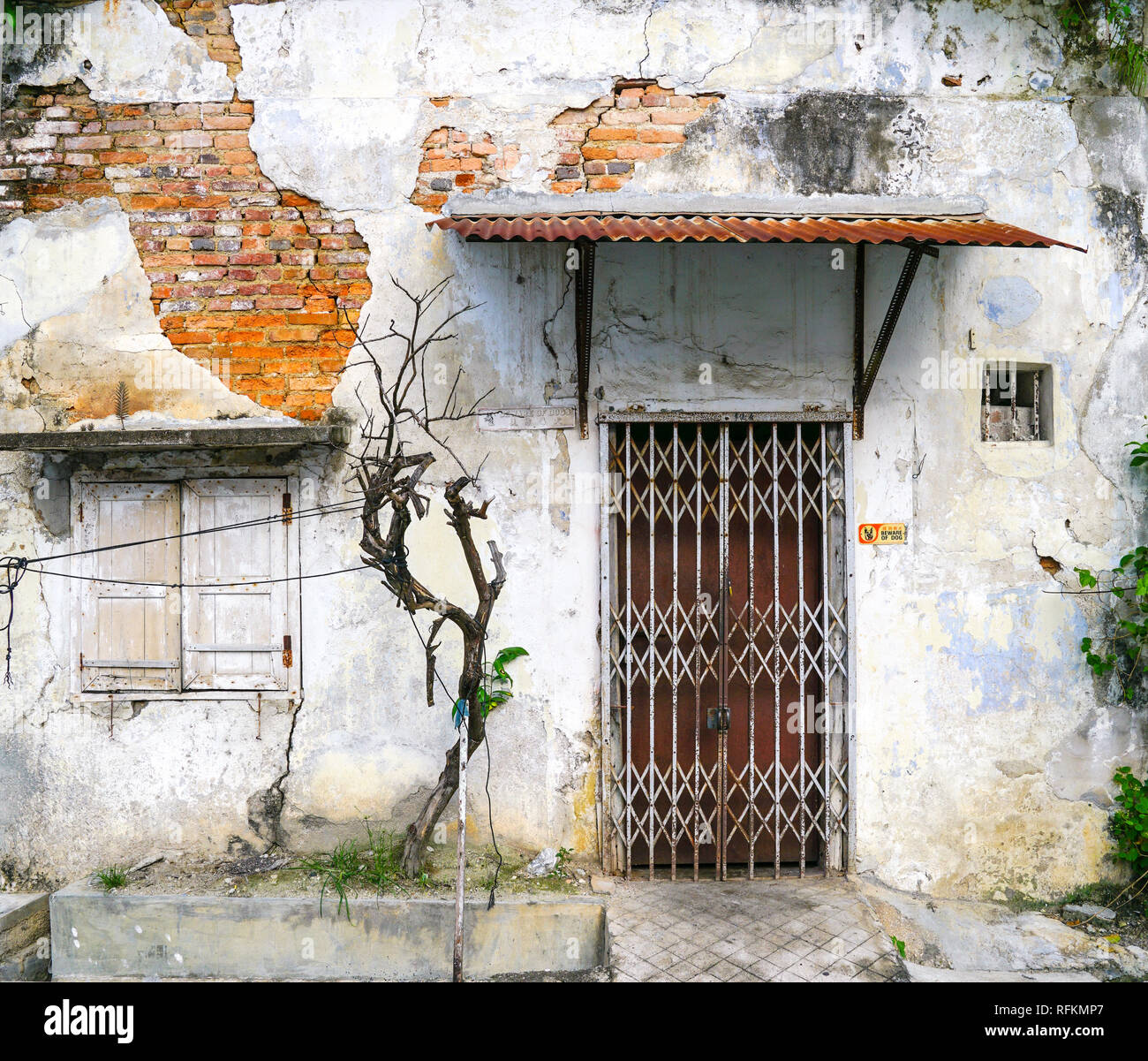 Old worn out wall with windows and door - Stock Image