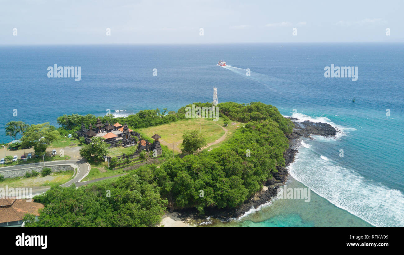 Aerial drone shot hill with temple at seascape in beautiful tourism location Padang Bai - Ba - Stock Image