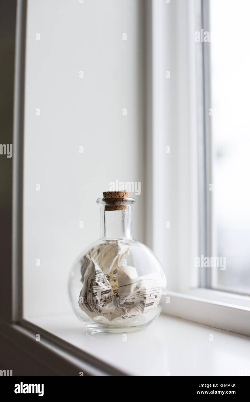 A crumpled piece of sheet music stuffed in a corked glass jar. - Stock Image