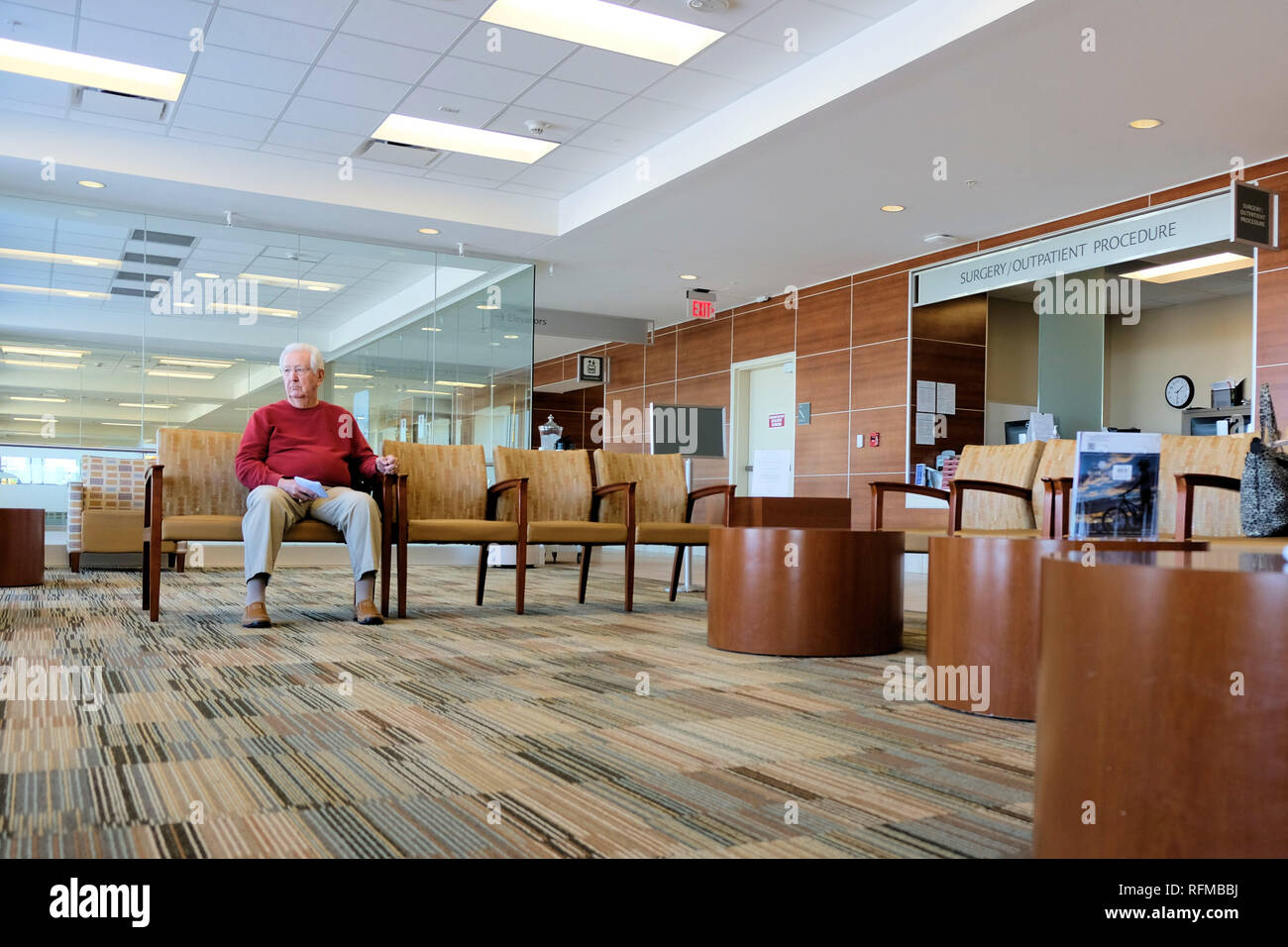Surgery Outpatient Procedure waiting area in a hospital; old man sitting in waiting area. - Stock Image