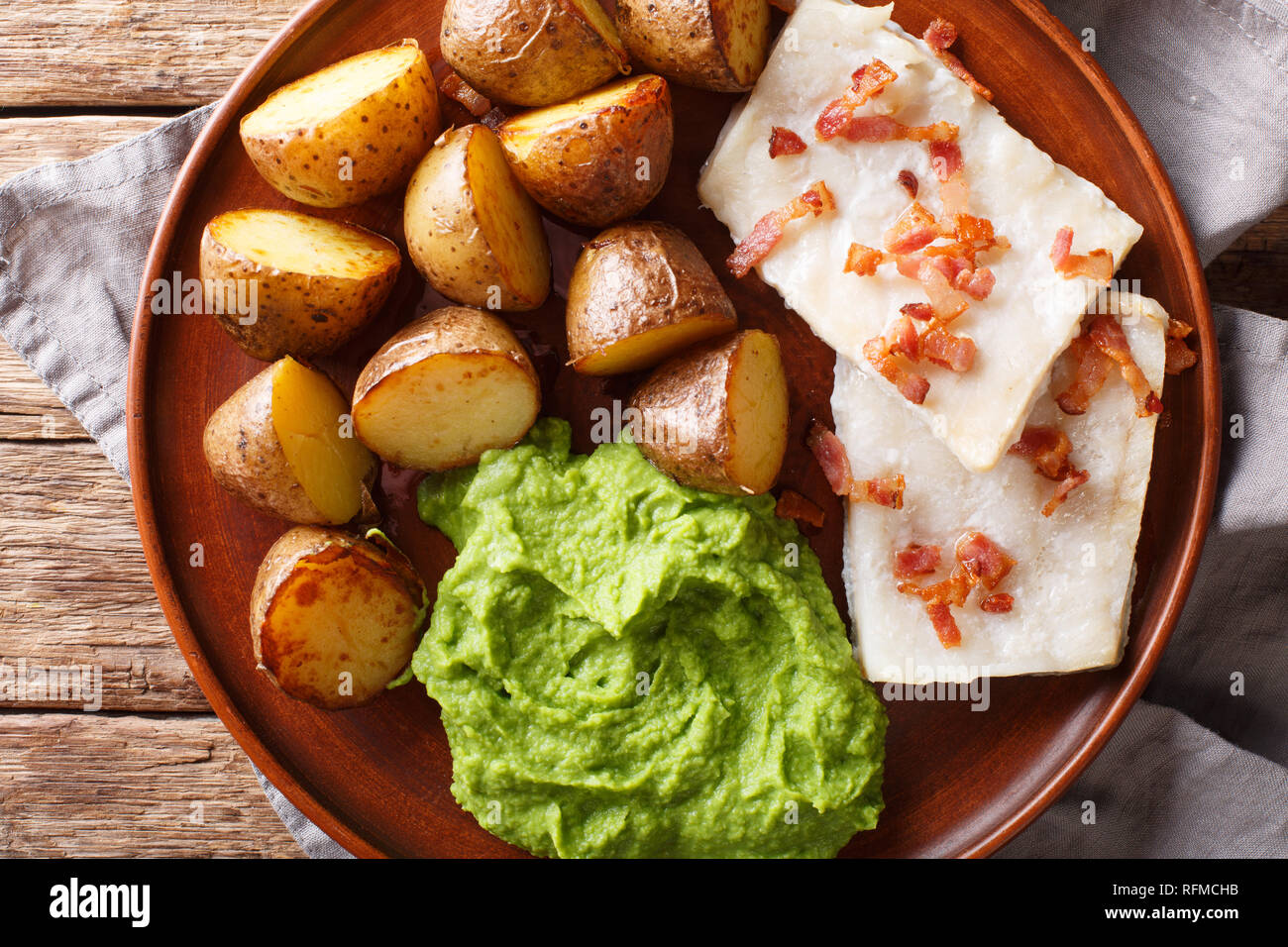 Organic codfish Lutefisk with pea puree, baked potatoes and bacon close-up on a plate on the table. Horizontal top view from above - Stock Image