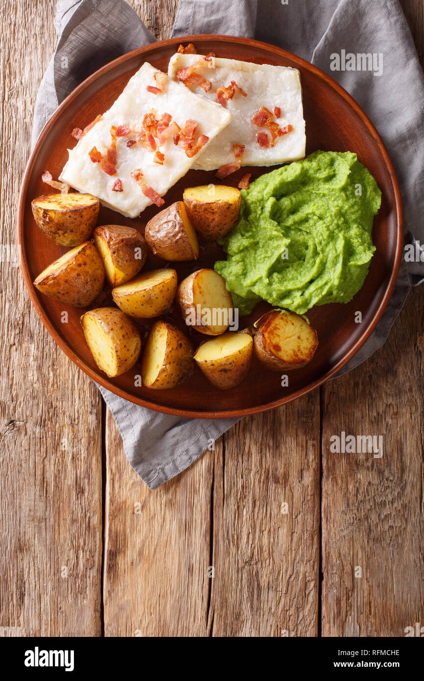 Popular Scandinavian food Lutefisk cod with pea puree, baked potatoes and bacon close-up on a plate on the table. vertical top view from above - Stock Image