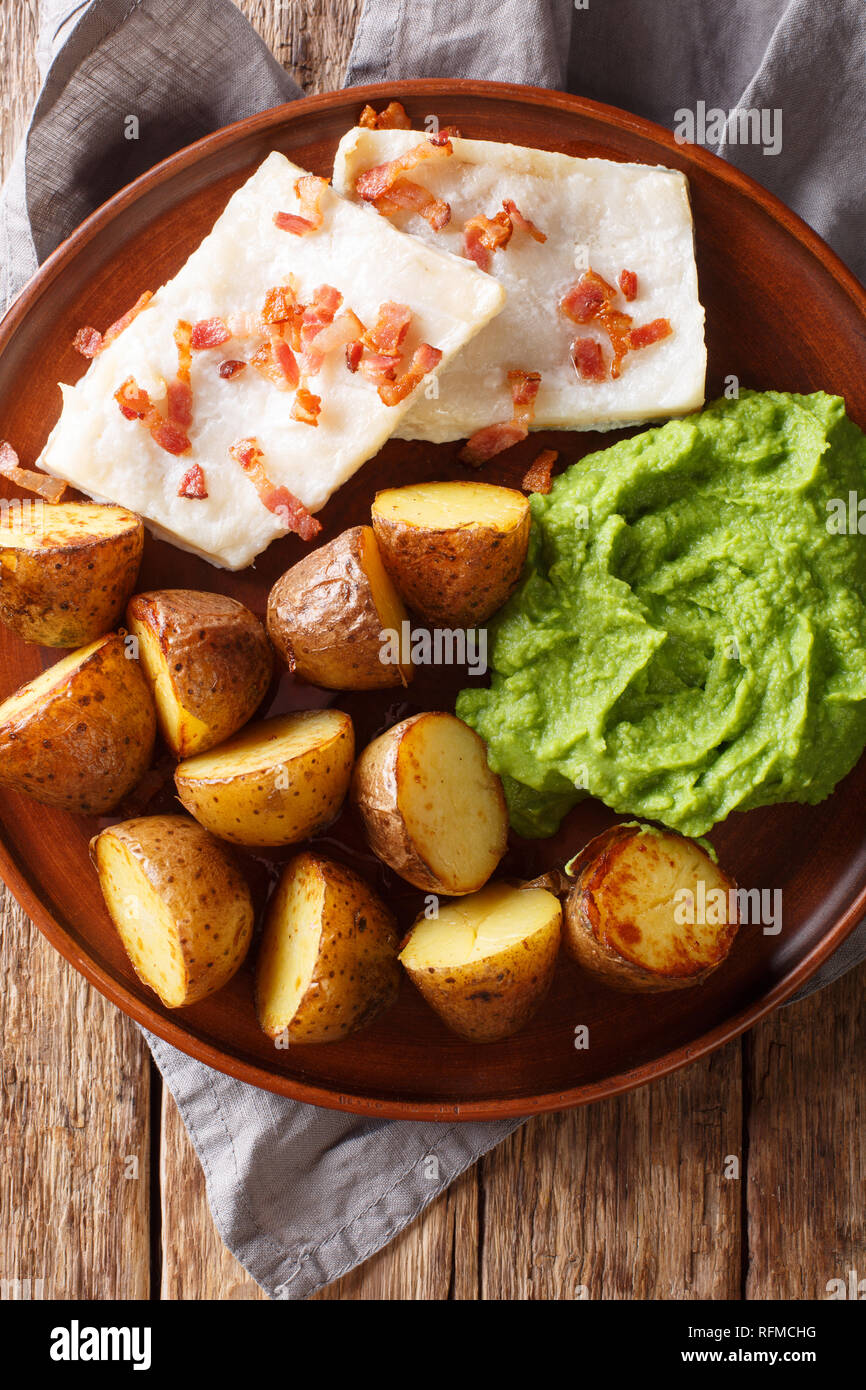 Organic codfish Lutefisk with pea puree, baked potatoes and bacon close-up on a plate on the table. vertical top view from above - Stock Image