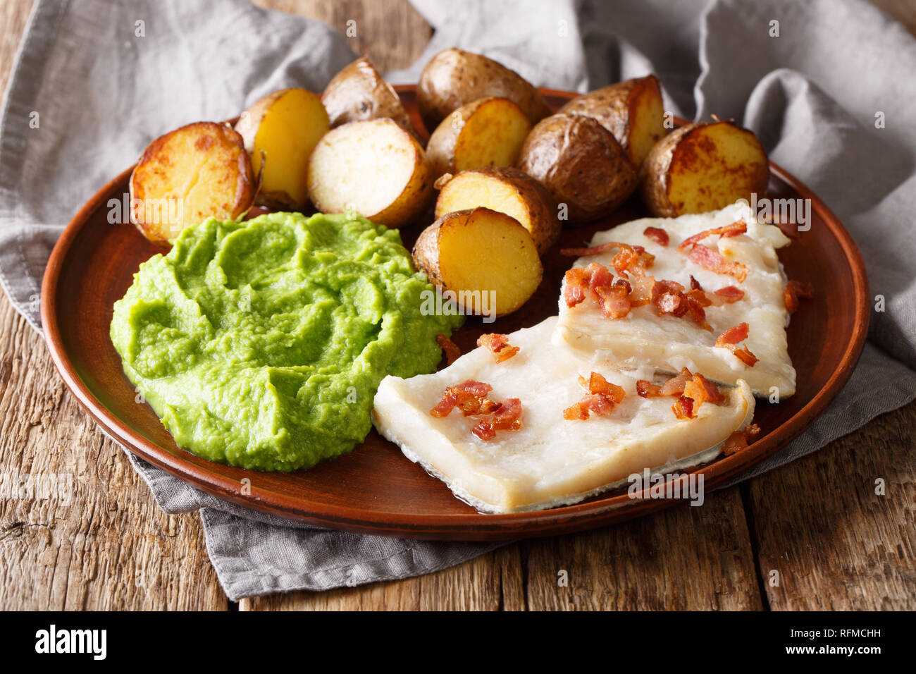 Traditional Scandinavian dish lutefisk served with pea puree, potatoes and bacon close-up on a plate. horizontal - Stock Image