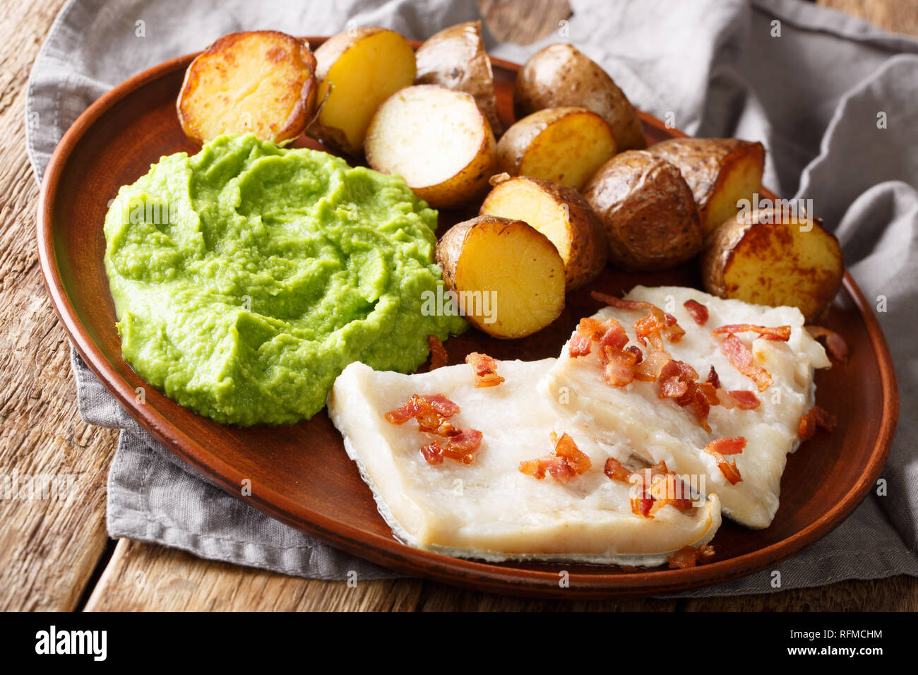 Norwegian cod lutefisk served with pea puree, potatoes and bacon close-up on a plate. horizontal - Stock Image