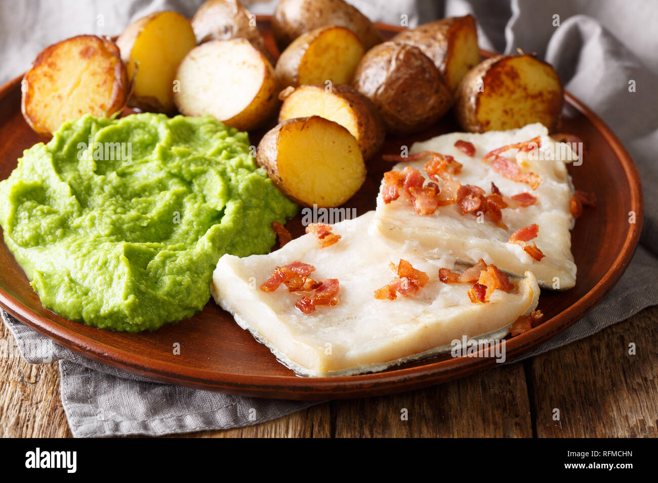 Cod Lutefisk with pea puree, baked potatoes and bacon close-up on a plate on the table. horizontal - Stock Image