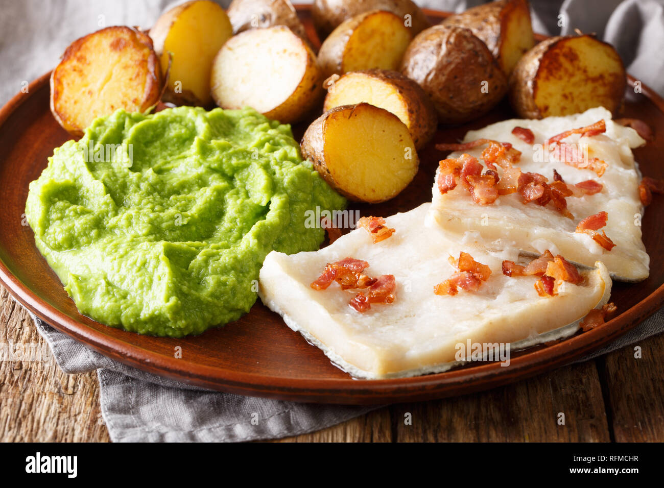 Popular Scandinavian food Lutefisk cod with pea puree, baked potatoes and bacon close-up on a plate on the table. horizontal - Stock Image