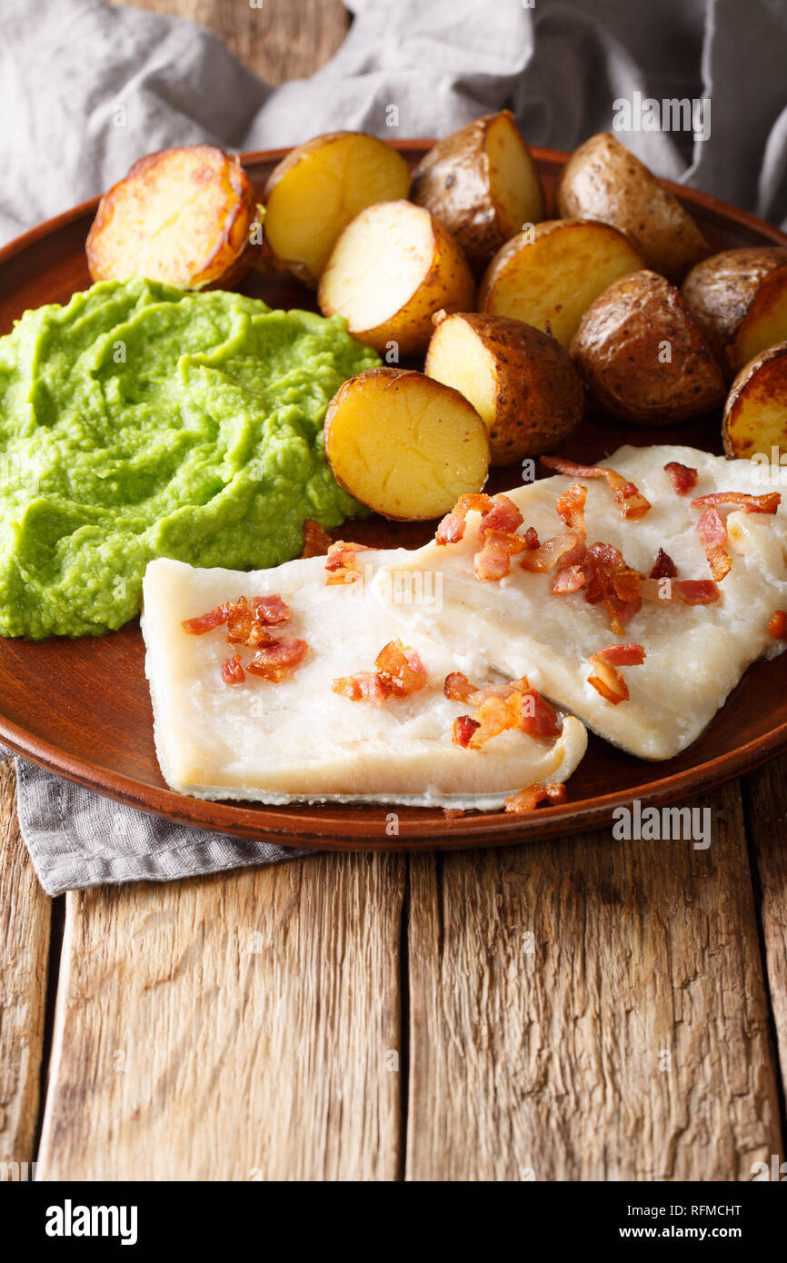 Rustic style Lutefisk with pea puree, baked potatoes and bacon close-up on a plate on the table. vertical - Stock Image