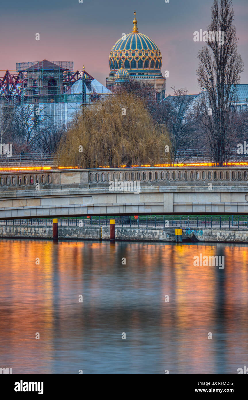 The river Spree in Berlin at sunset with the cupola of the New Synagogue in the back Stock Photo