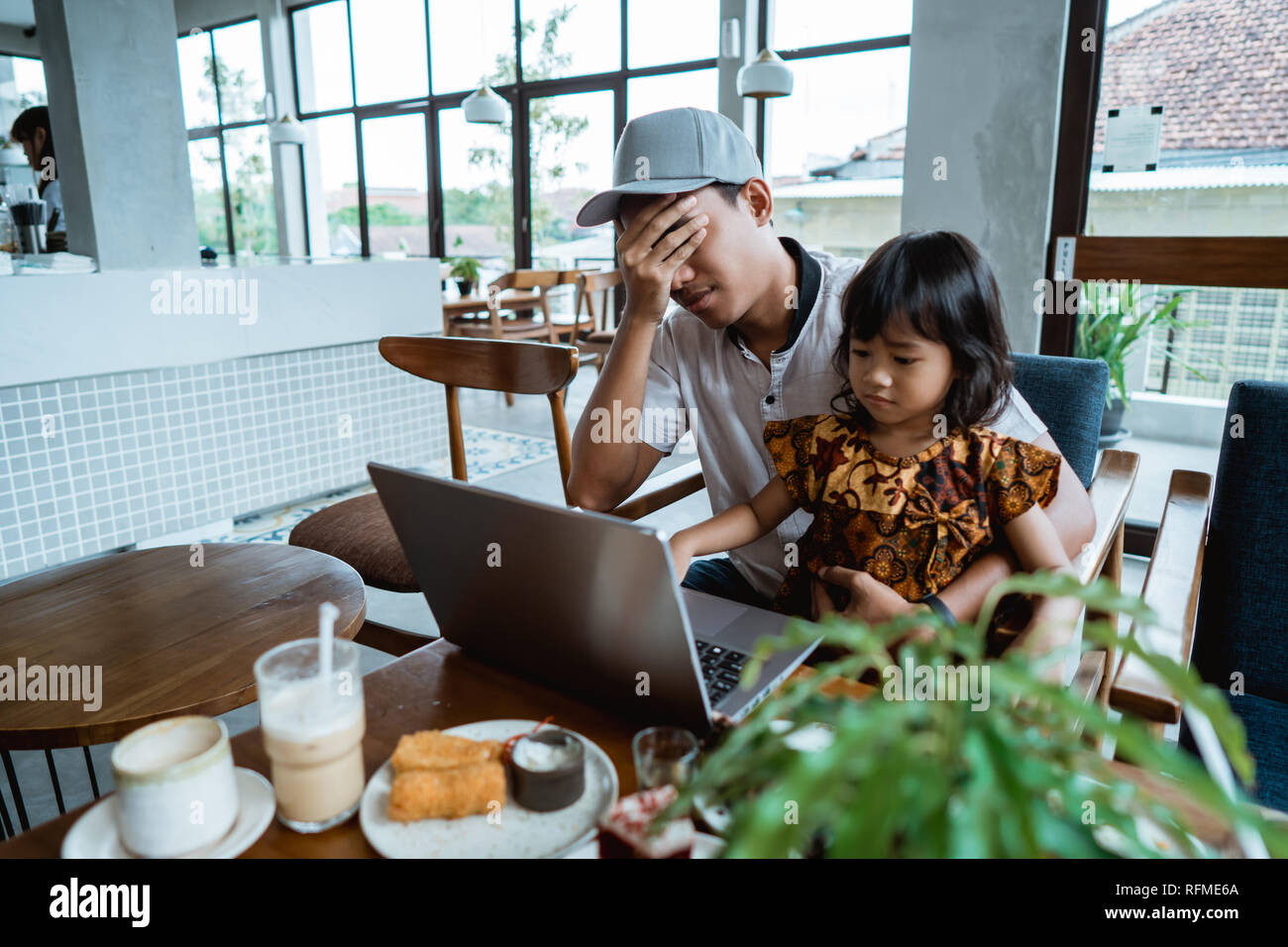 child disturb her dad while working - Stock Image