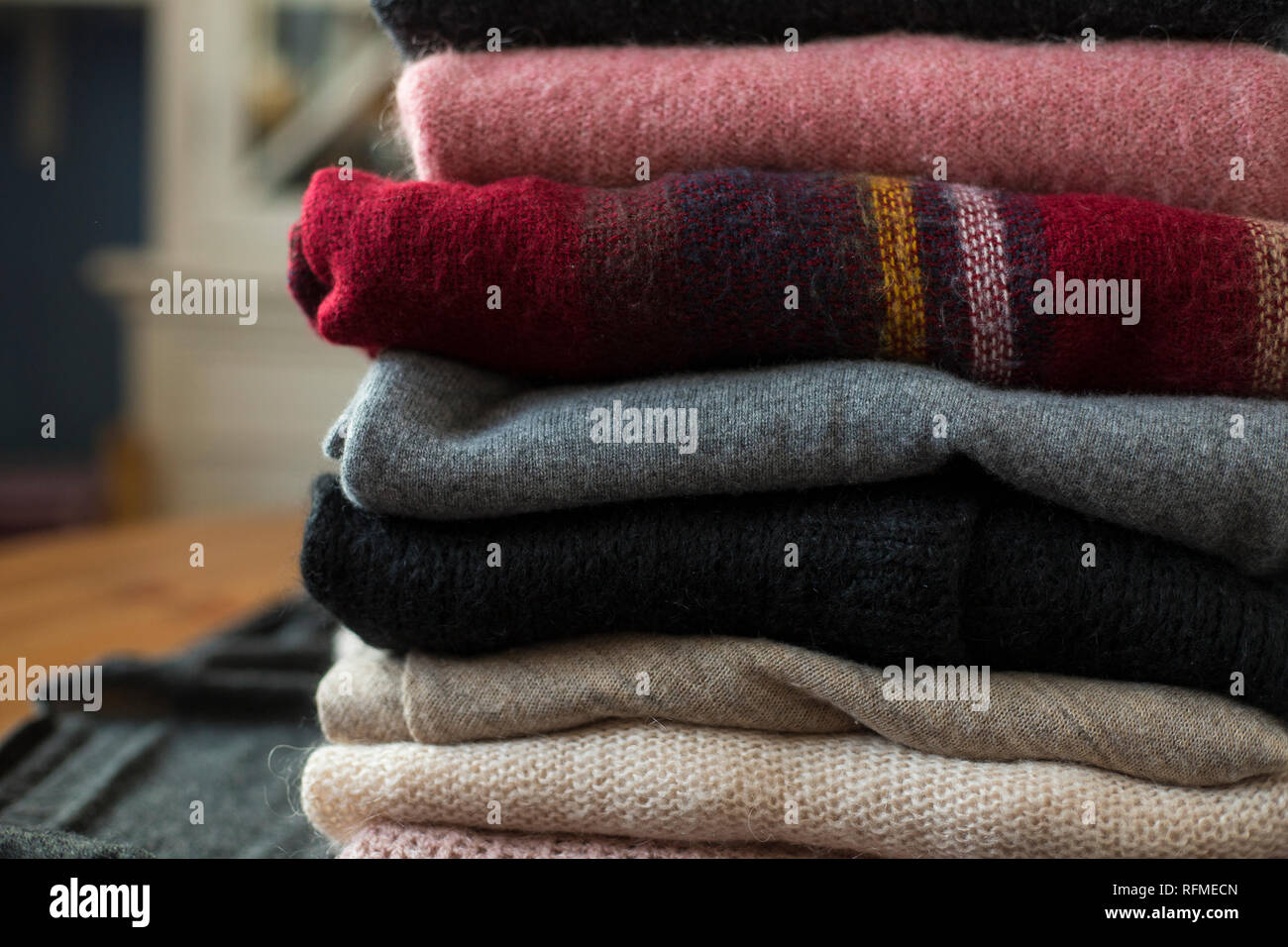 Pile of pink and grey sweaters close-up background. - Stock Image