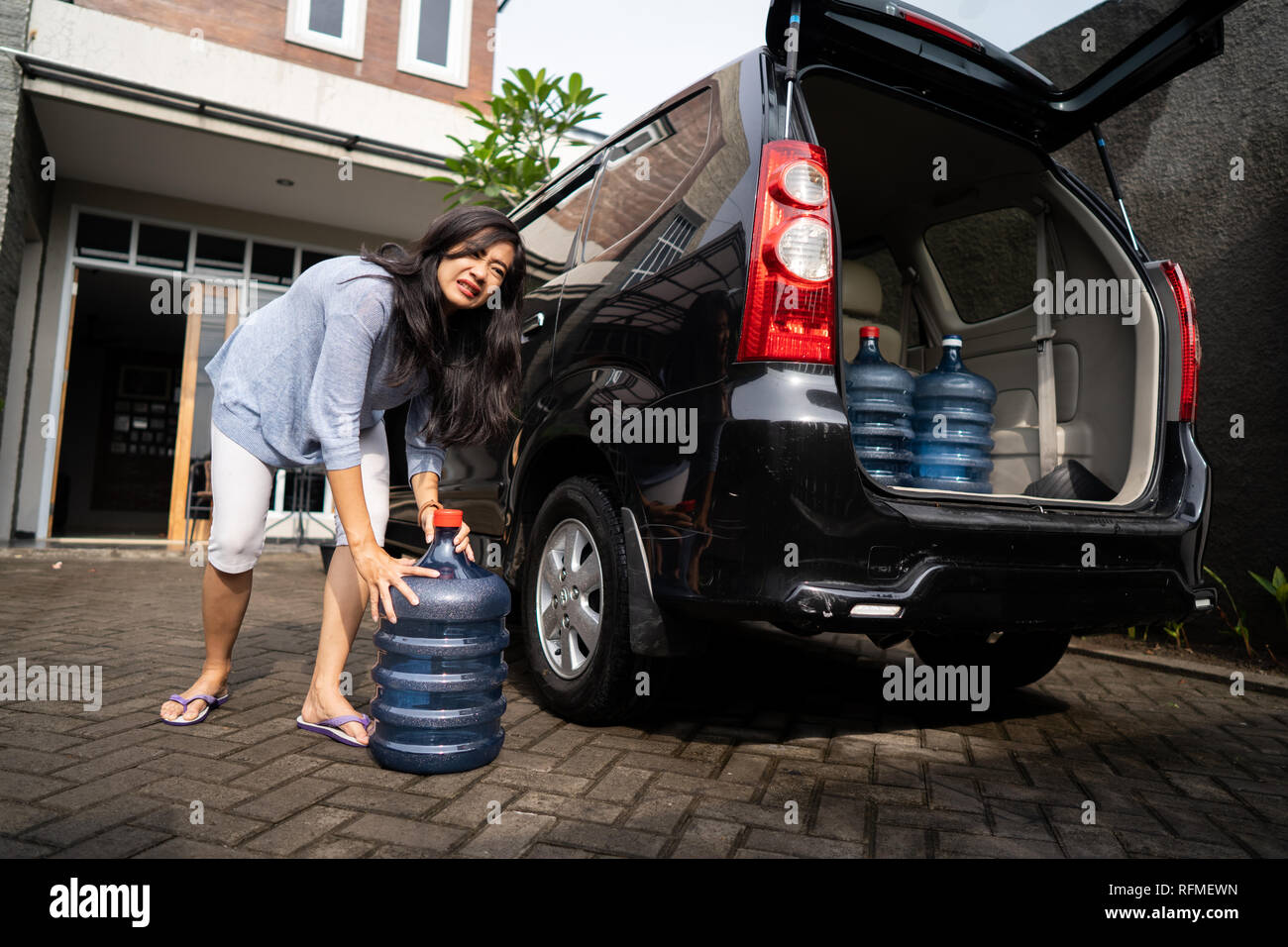 unhappy woman carrying a gallon of water - Stock Image
