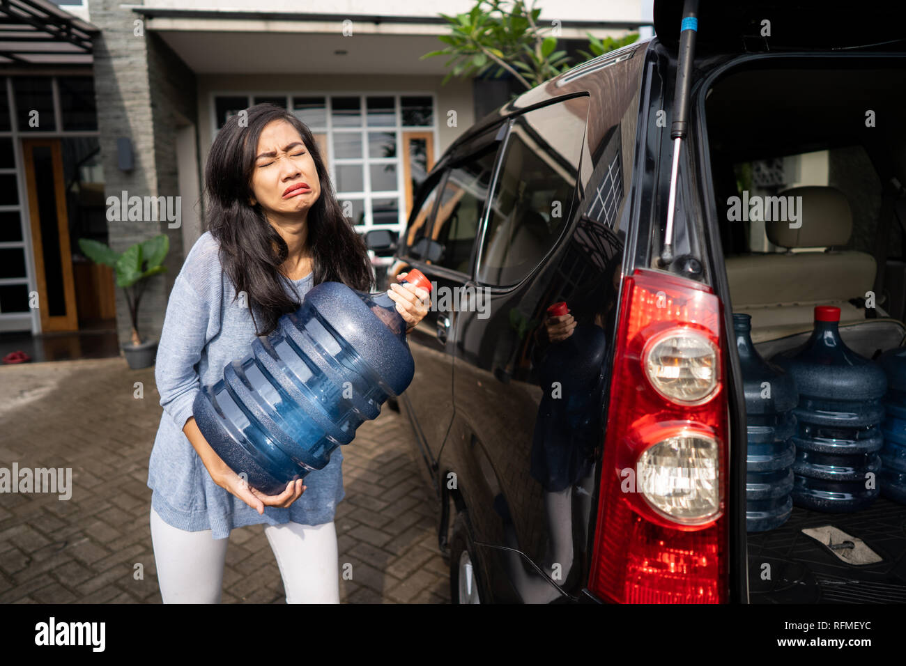 upset woman try to carry gallon of water - Stock Image