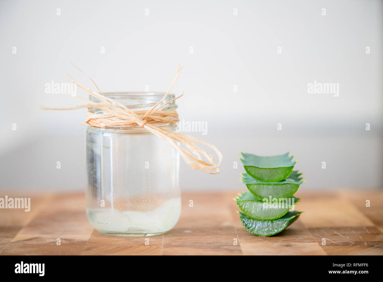 Essence from aloe vera plan in cosmetic bottle with slices of plant stacked on top of each other on the side and space for text - Stock Image