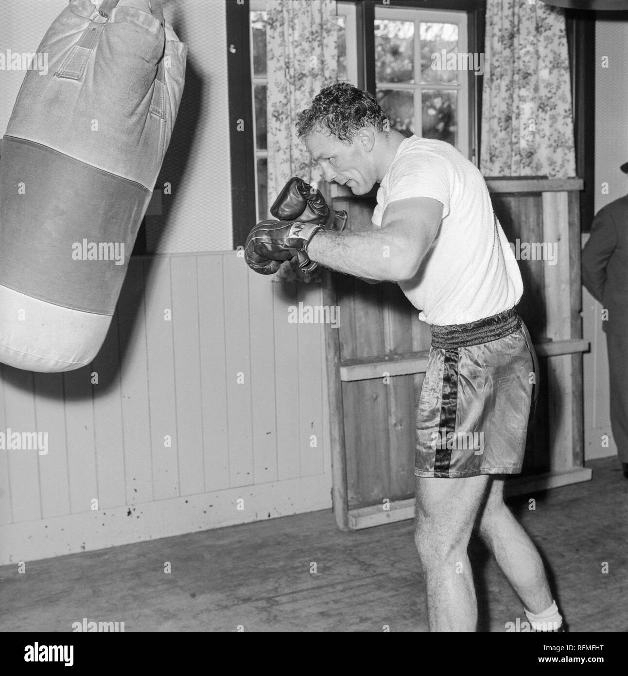 English heavyweight boxer Henry Cooper trying in a gym in England during the 1960s. - Stock Image