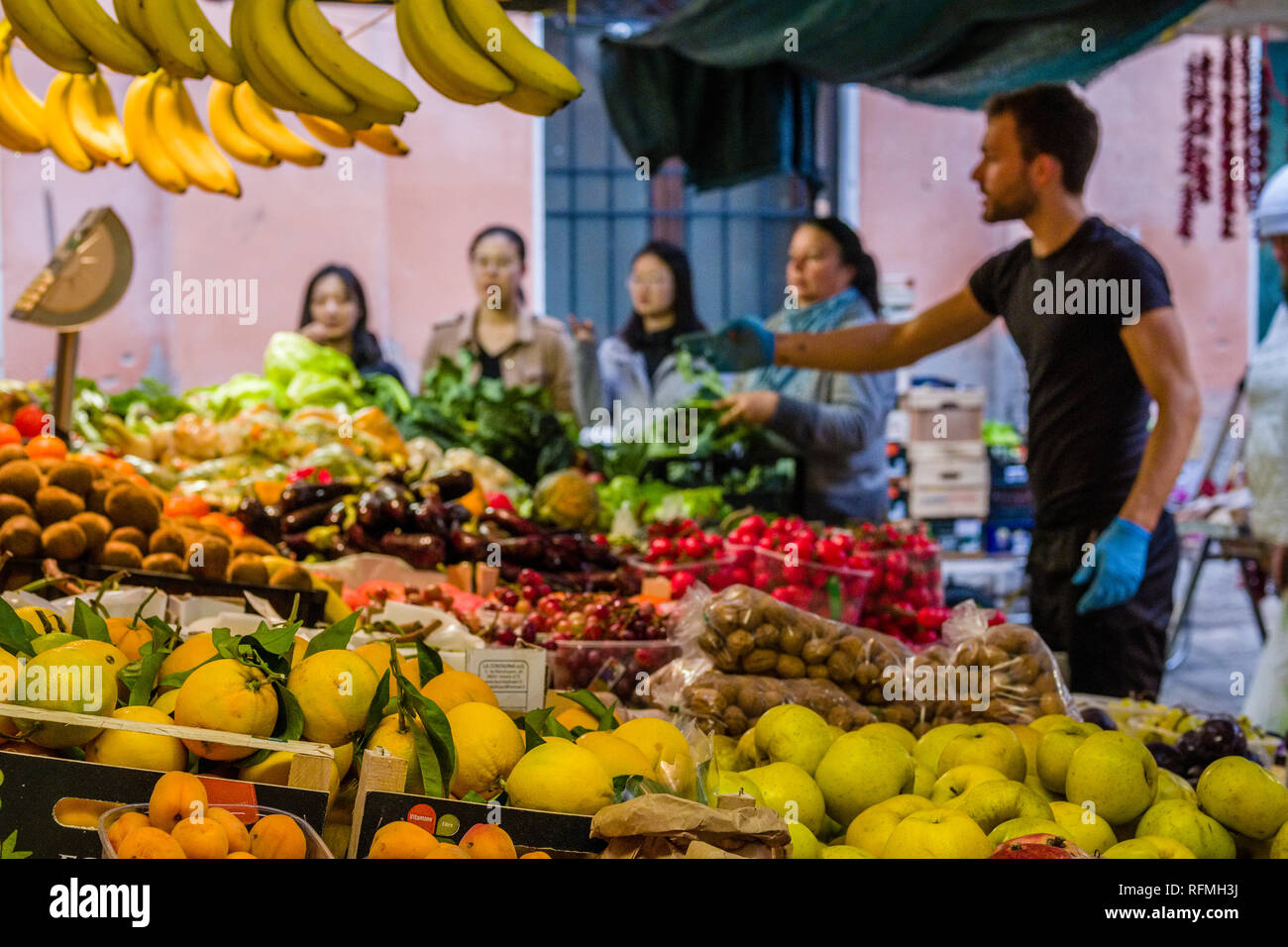 Market trader is selling fruits and vegetables at Rialto Market, Mercato di Rialto to tourists - Stock Image