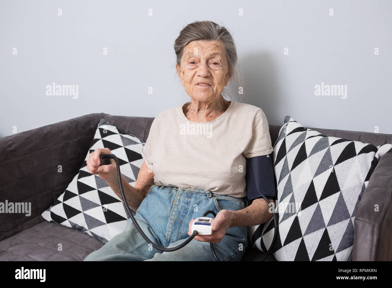 The topic is very old person and health problems. A senior Caucasian woman, 90 years old, with wrinkles and gray hair, sits home on sofa and uses bloo - Stock Image